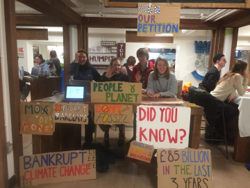 "Photograph of four students at a table with signs reading ""sign our petition"", ""bankrupt climate change"" etc."