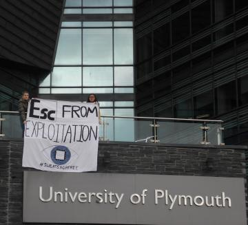 "Photograph of two students holding a banner which reads ""Esc from exploitation"" outside the University of Plymouth"