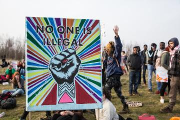 Solidarity fist on a placard saying 'No one is illegal
