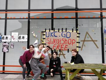 students in front of sweatshop free banner