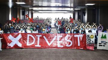 Vietnamese climate activists behind a large banner saying 'DIVEST'