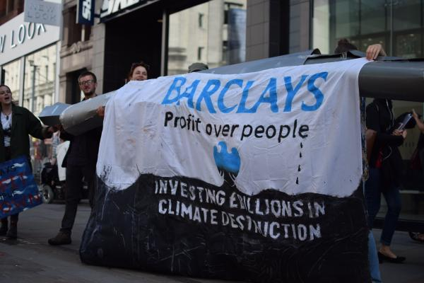 Students hold a banner saying Barclays. Profit over people.