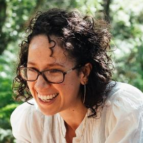 This text is Pcture of Che, laughing. She is dressed in white top, with dark curly hair and glasses, and sitting with green foliage behind her.