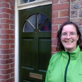 Image of Virginia, in a green jacket, with brown hair and glasses, smiling, standing by a door with number 3 on it (Her home in York when she was a student)